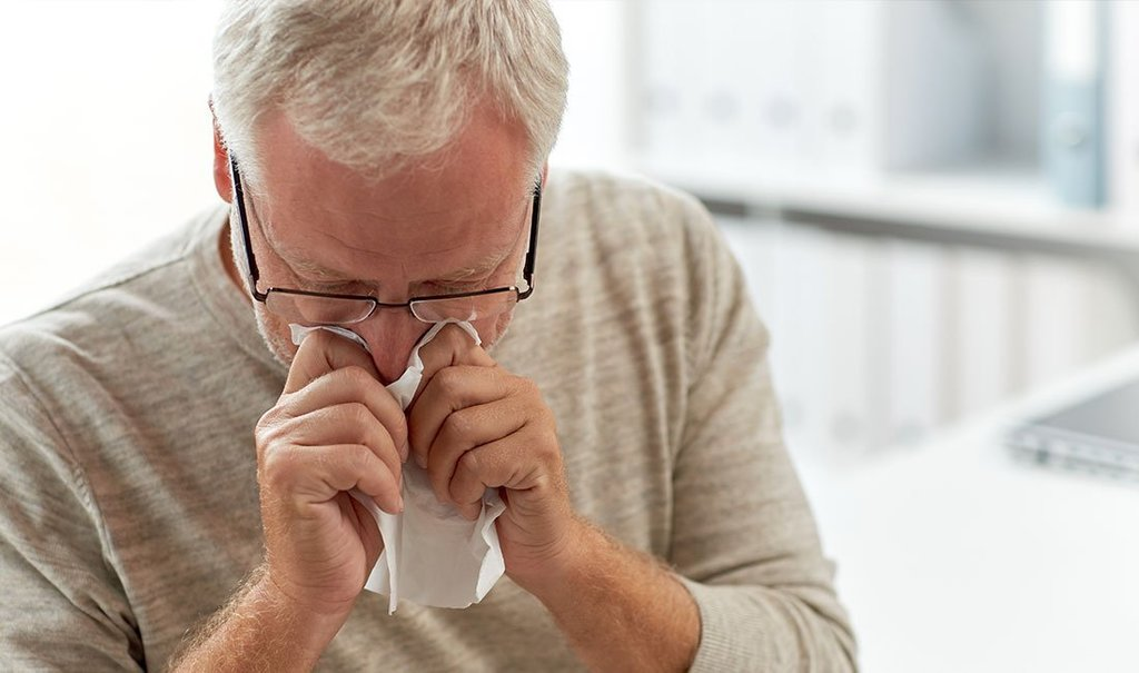 Senior man blowing nose with napkin