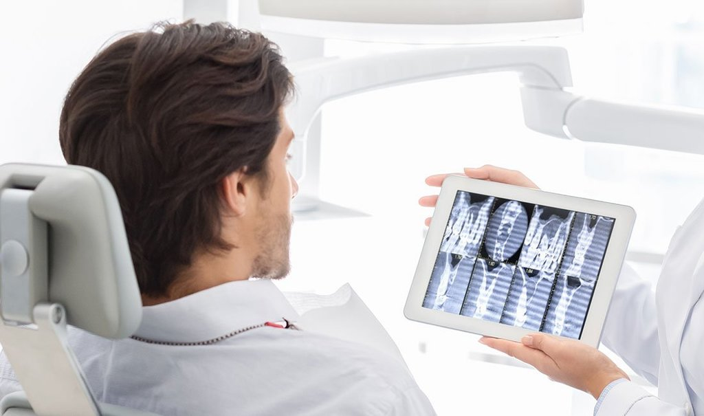 Dentist showing patient x-ray results on digital tablet