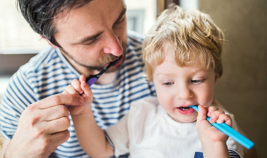 Father brushing his teeth with a toddler boy at home.